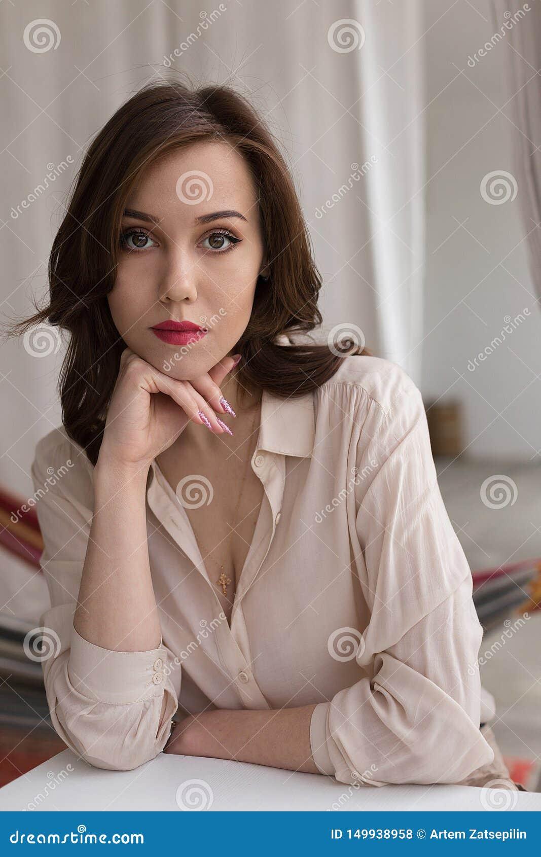 Den härliga caucasian flickan med röda kanter i stilfull beige blus ser hänsynsfullt in i kameran som lutar på tabellen i kafé