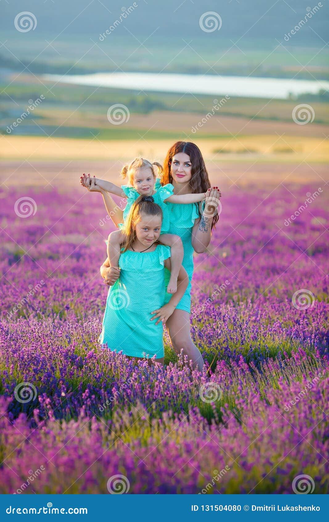 Den härliga familjen av gulliga flickor tycker om på liv med ängen för solnedgången för flickamakt av lavendel Gå mamman och dött