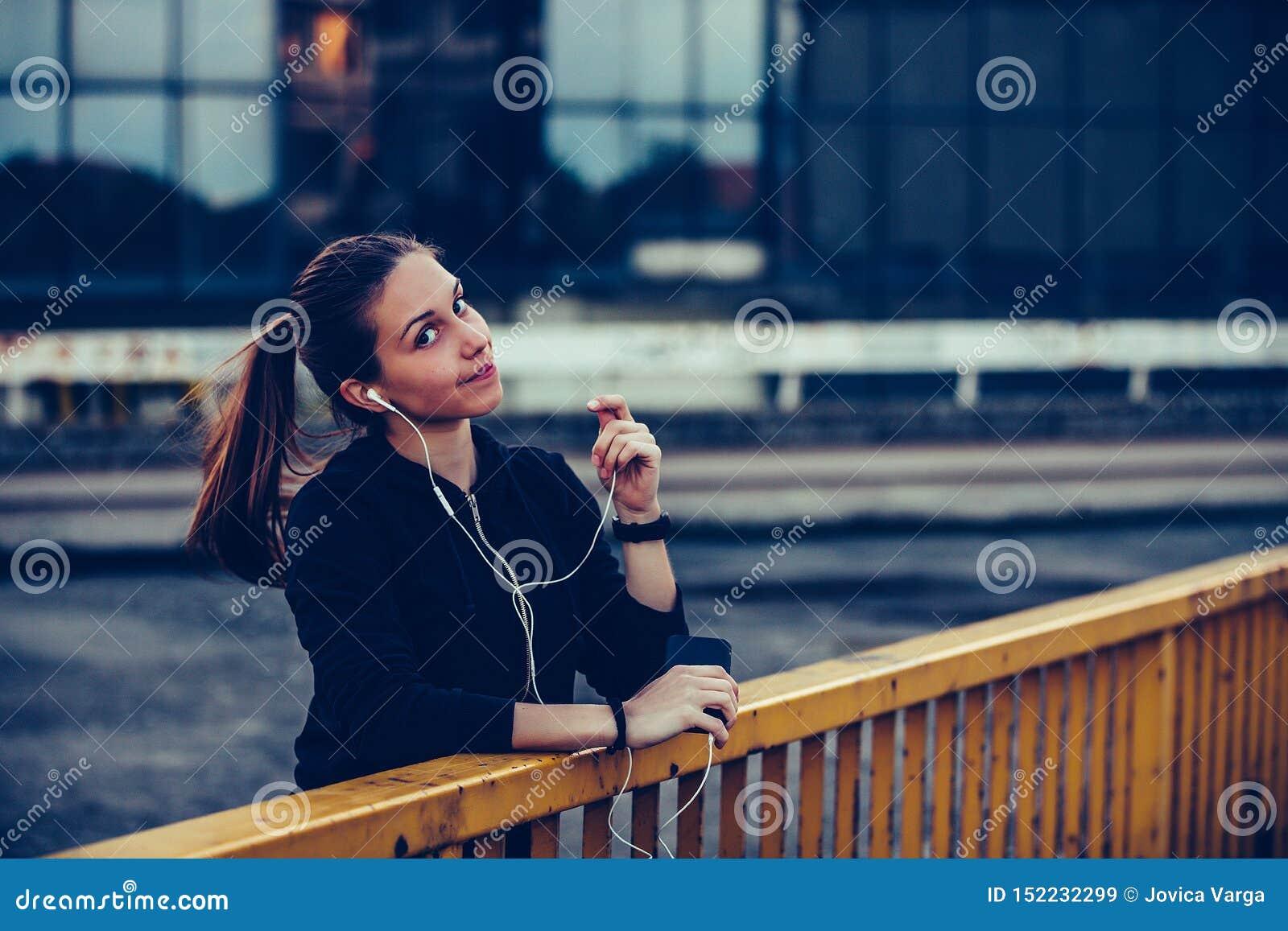 Den härliga flickan i svarta sportar utrustar att vila, når han har kört på bron