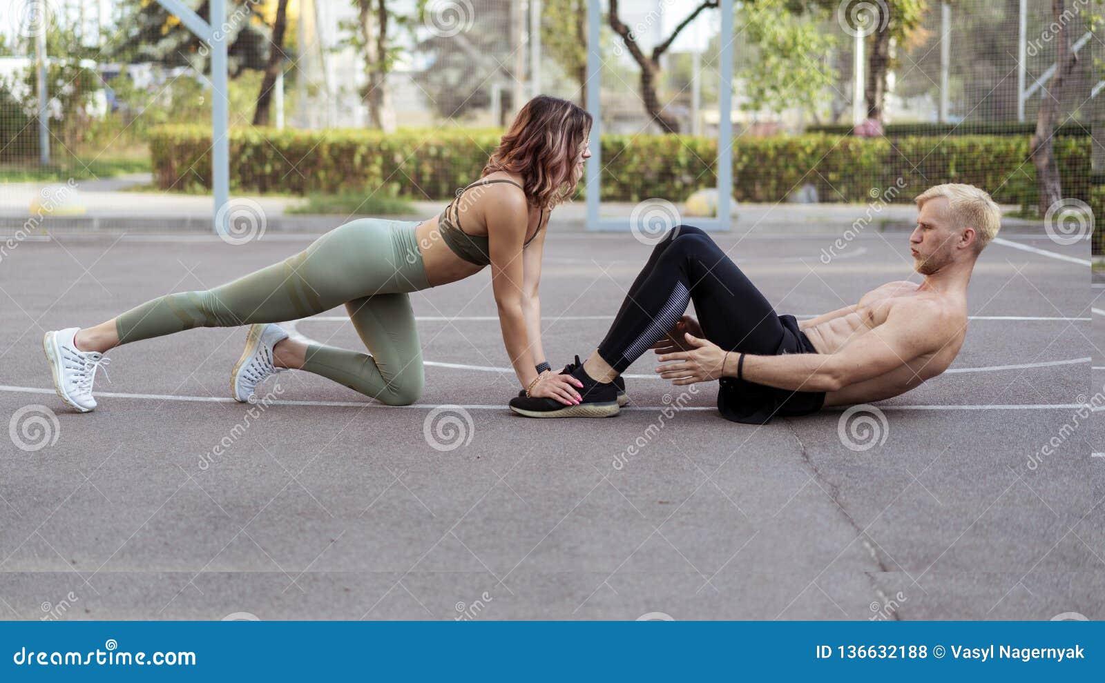 Den härliga flickan som hjälper den stiliga mannen, medan att göra sitter, ups