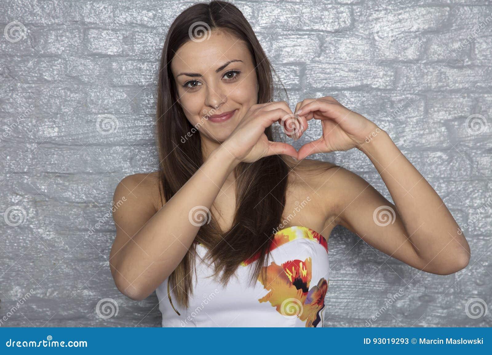 Den härliga flickan visar hjärta med handen