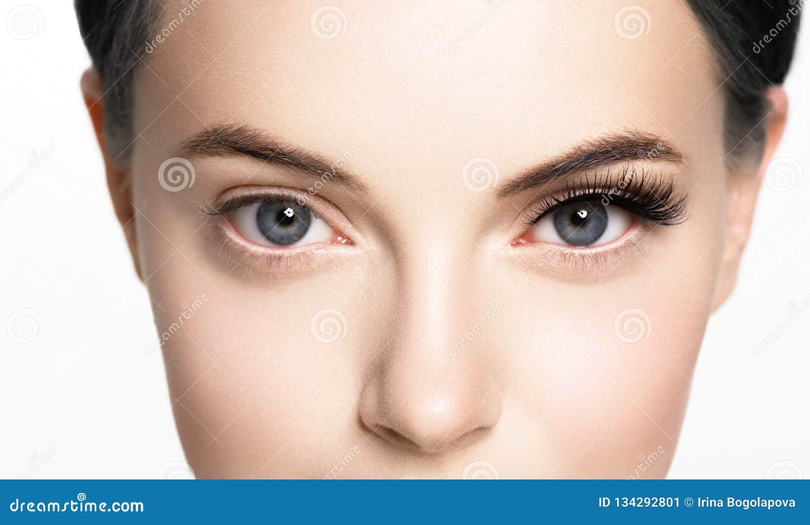 Den härliga kvinnaframsidan med ögonfrans piskar hud för skönhet för förlängningen före och efter sund som naturlig makeup stängd