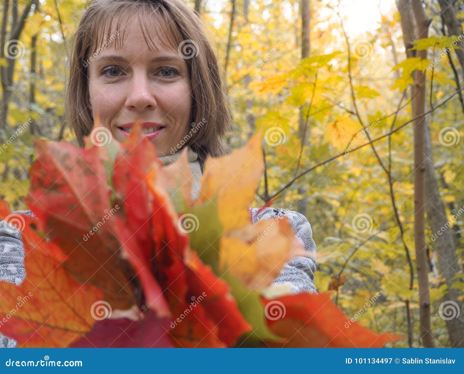 Den härliga kvinnan i lag i parkera samlar lönnlöv höst som samlar leaveskvinnan