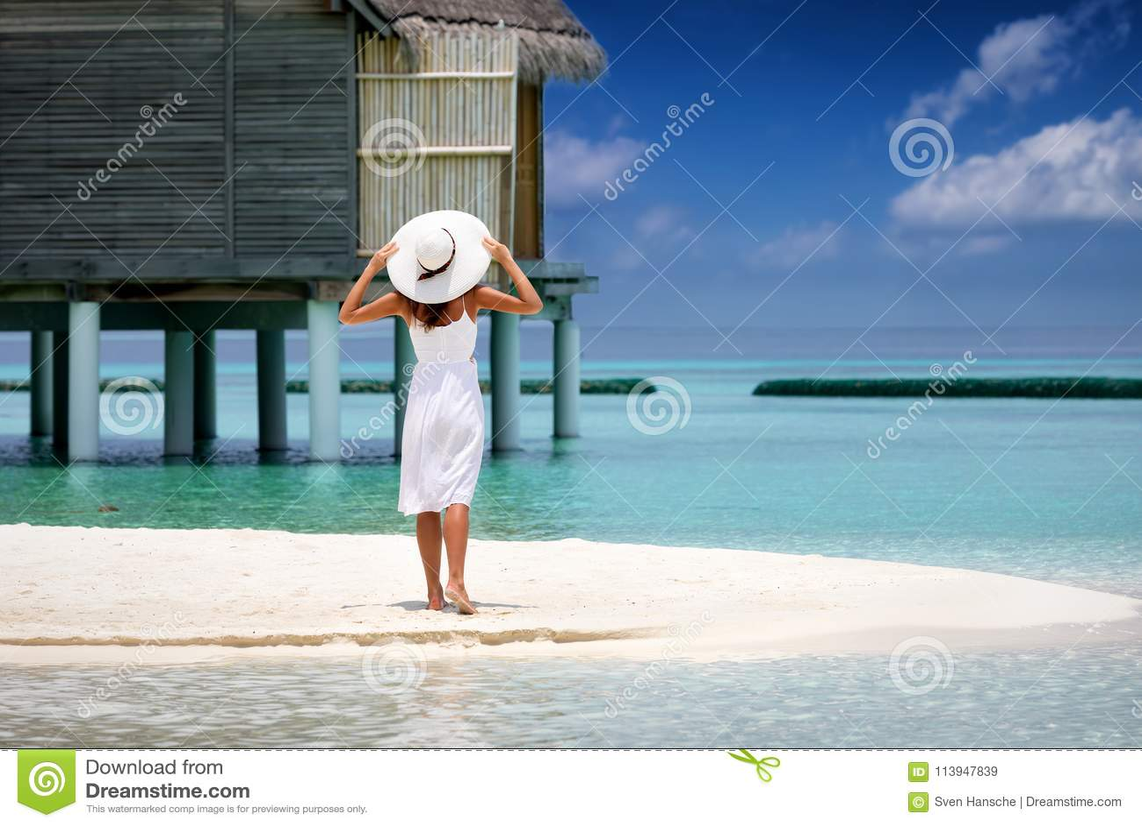 Den härliga kvinnan i den vita klänningen står på en strand i Maldiverna