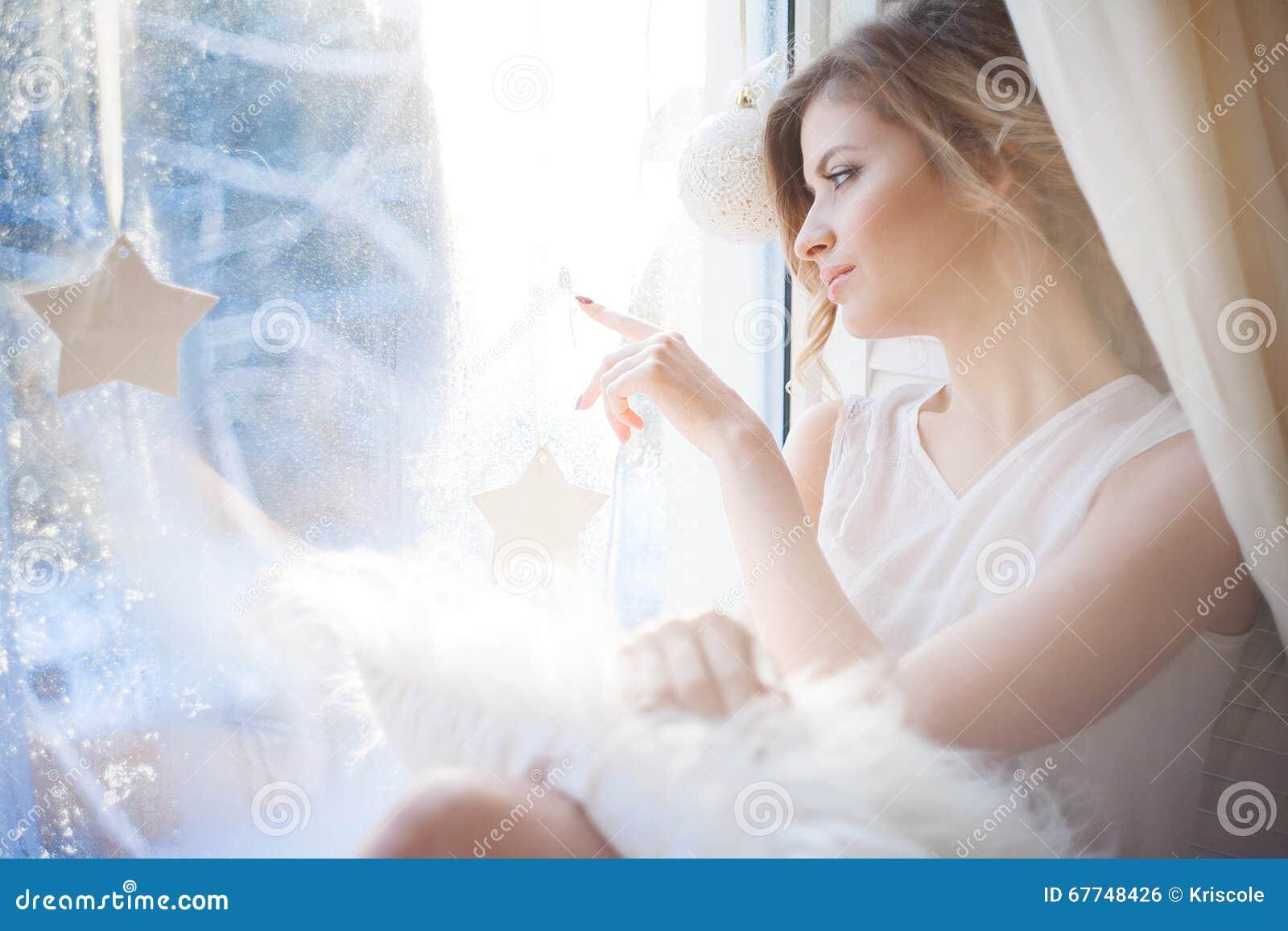 Den härliga kvinnan med ny daglig makeup och romantiska krabba frisyren som sitter på fönsterbrädan, drar på exponeringsglas