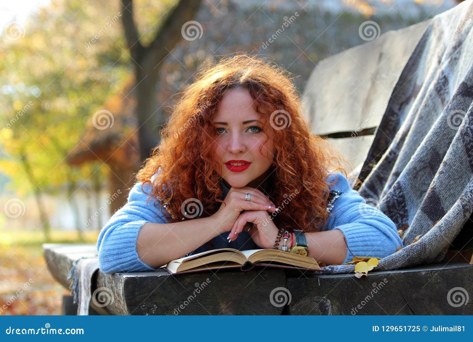 Den härliga kvinnan med rött hår ligger på en bänk med en bok och gula sidor och ser in i kameran Autumn Park Backgroun