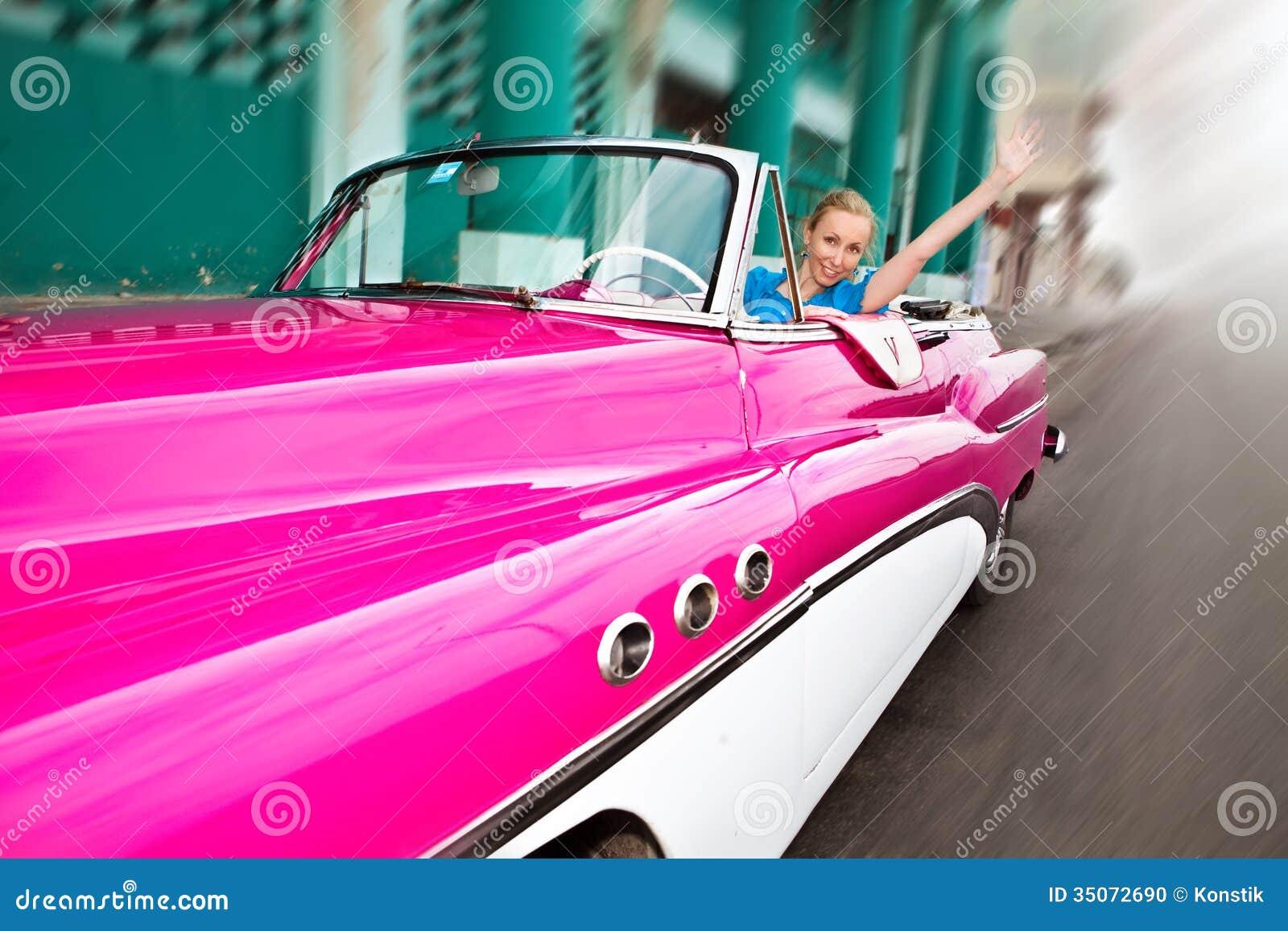 Den härliga kvinnan på en gammal amerikansk retro bil för hjul i den gamla havannacigarren, Kuba