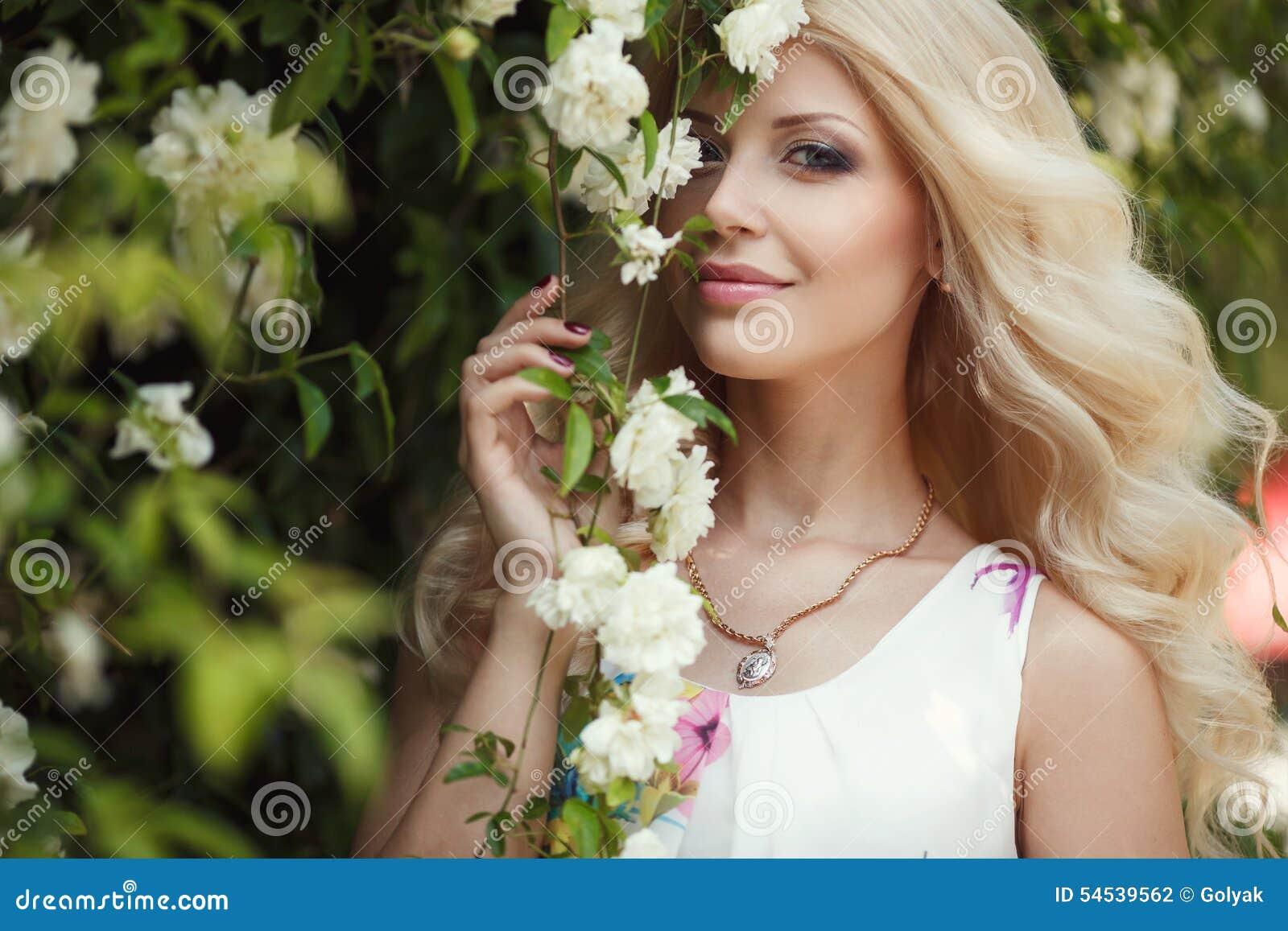 Den härliga kvinnan parkerar in nära Bush de blommande rosorna