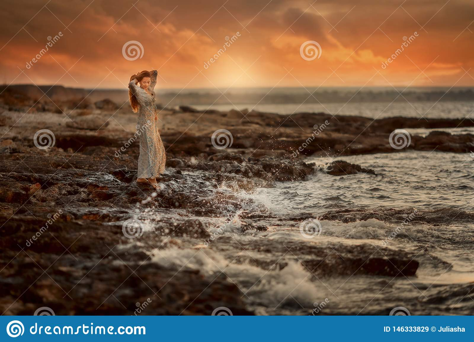 Den härliga kvinnan vaggar in kusten på soluppgång