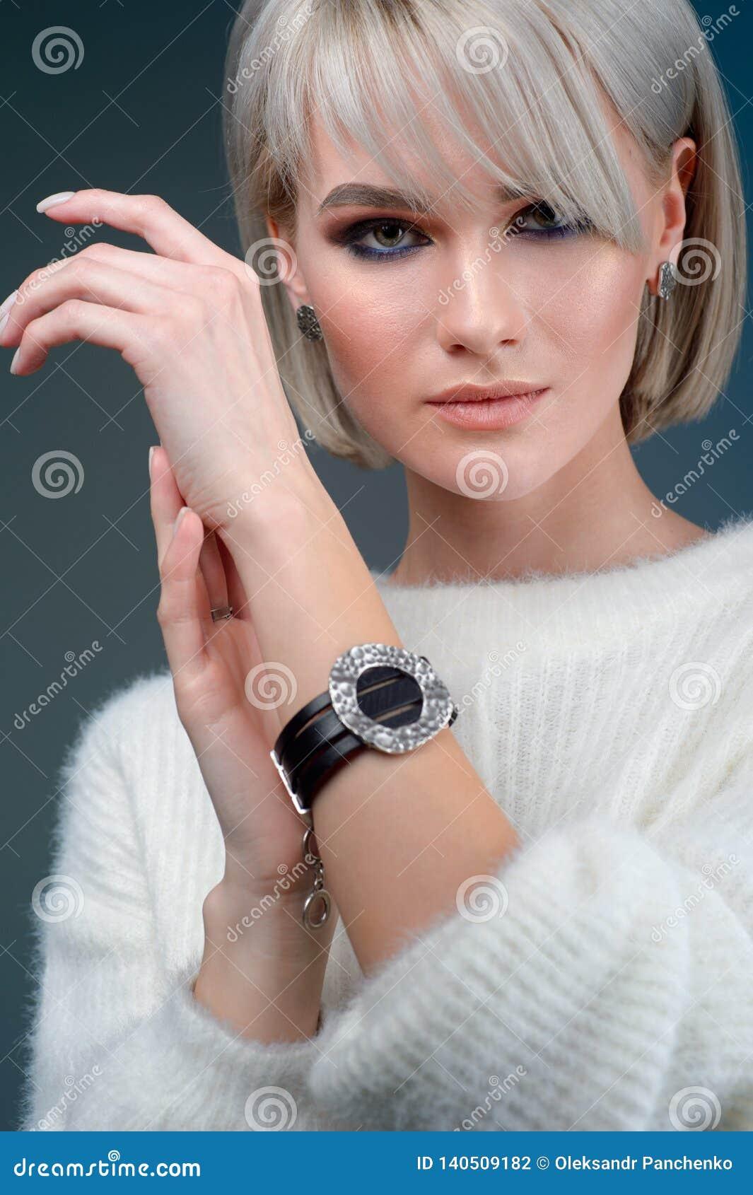 Den härliga kvinnan visar armbandet på handen på blå bakgrund