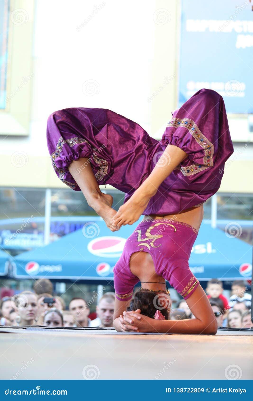 Den härliga kvinnan visar in yoga på etappen