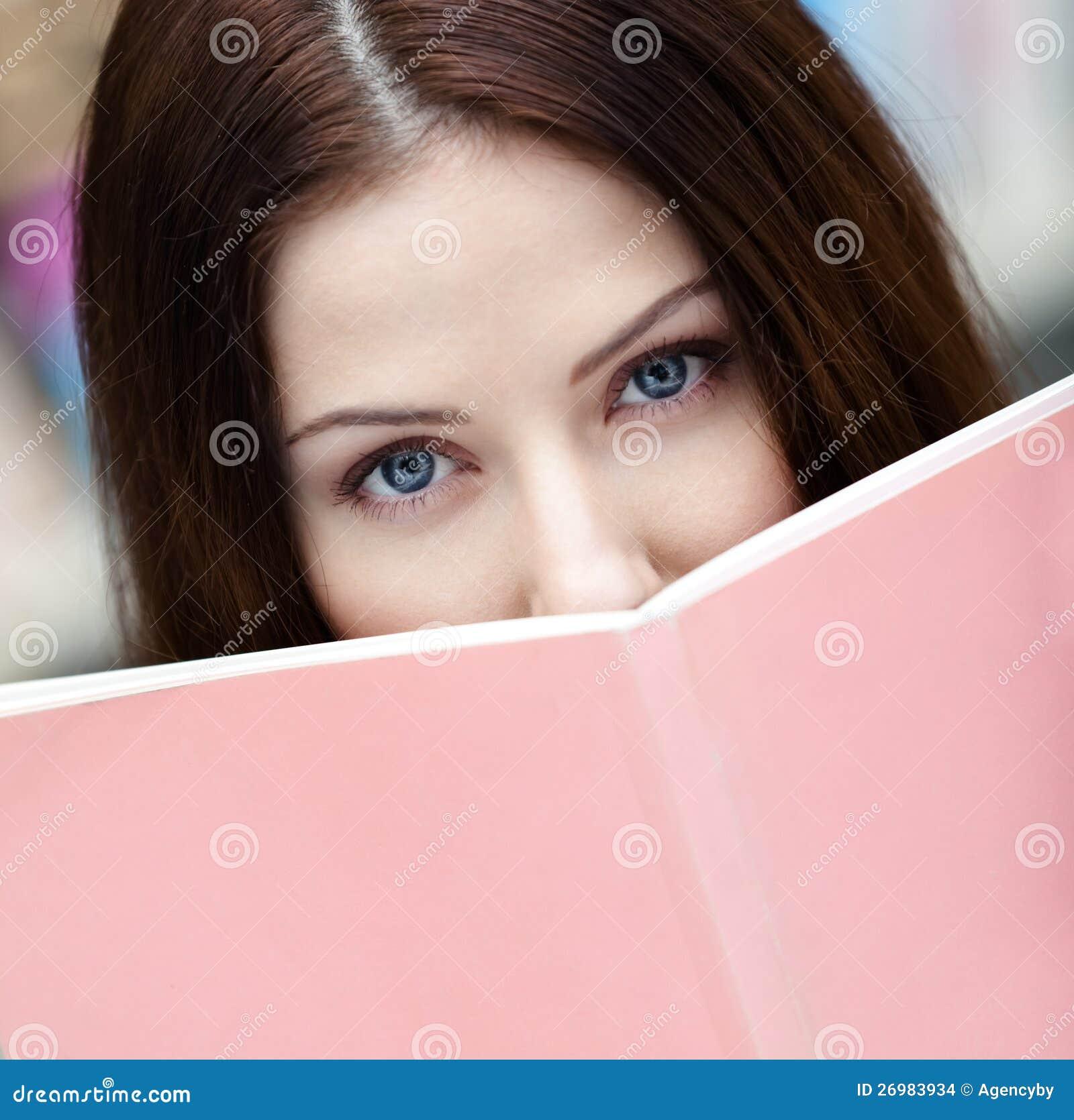 Den härliga kvinnliga deltagaren läser boken