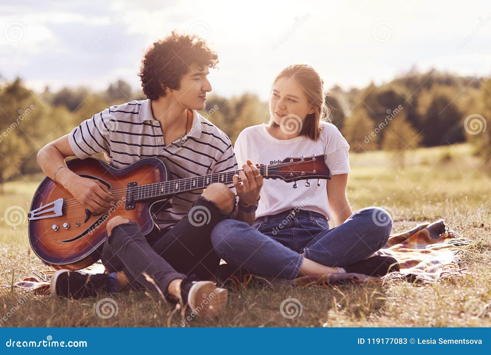 Den härliga kvinnlign ser med förälskelse, och lycka på hennes pojkvän, som spelar gitarren och sjunger romantiska sånger till vä