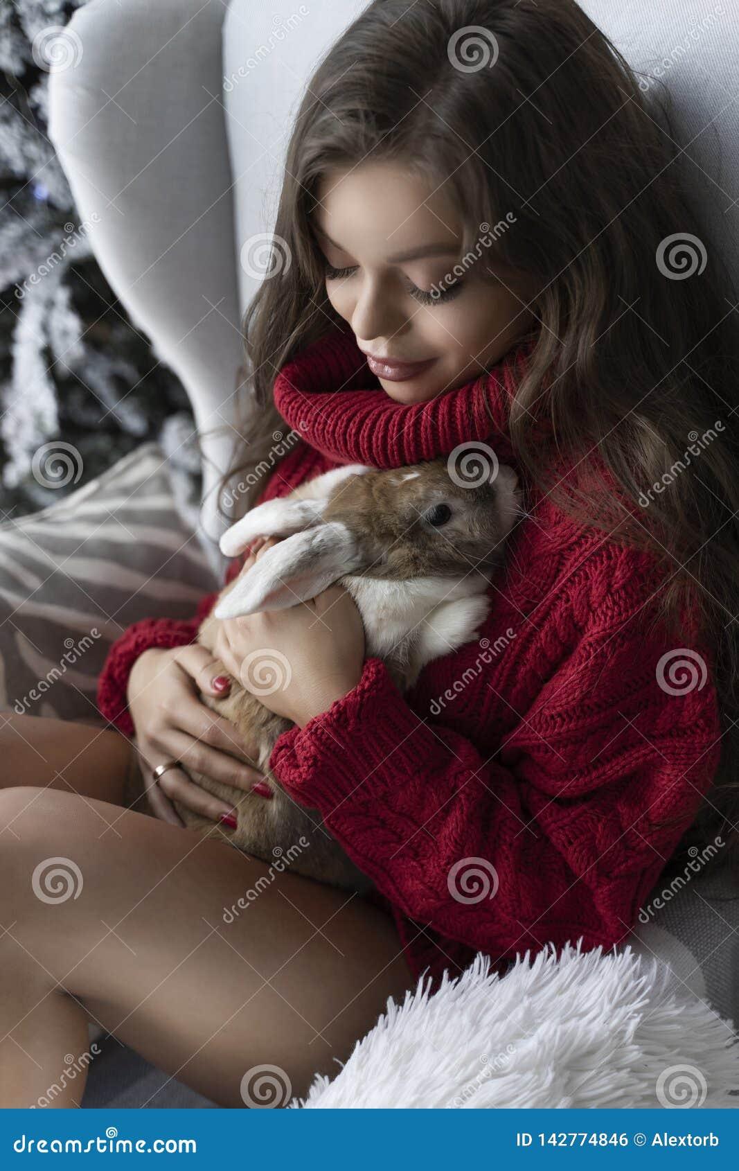 Den härliga långbenta unga flickan, den bärande röda tröjan och ullsockor sitter på fönstret och rymmer försiktigt en kanin i hen