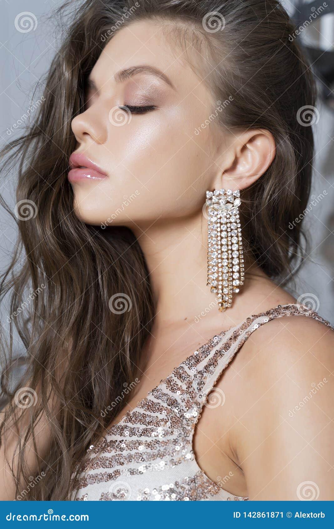 Den härliga långbenta unga sexiga eleganta flickan med stora bröst och att bära en briljant åtsittande klänning och stiletter sit