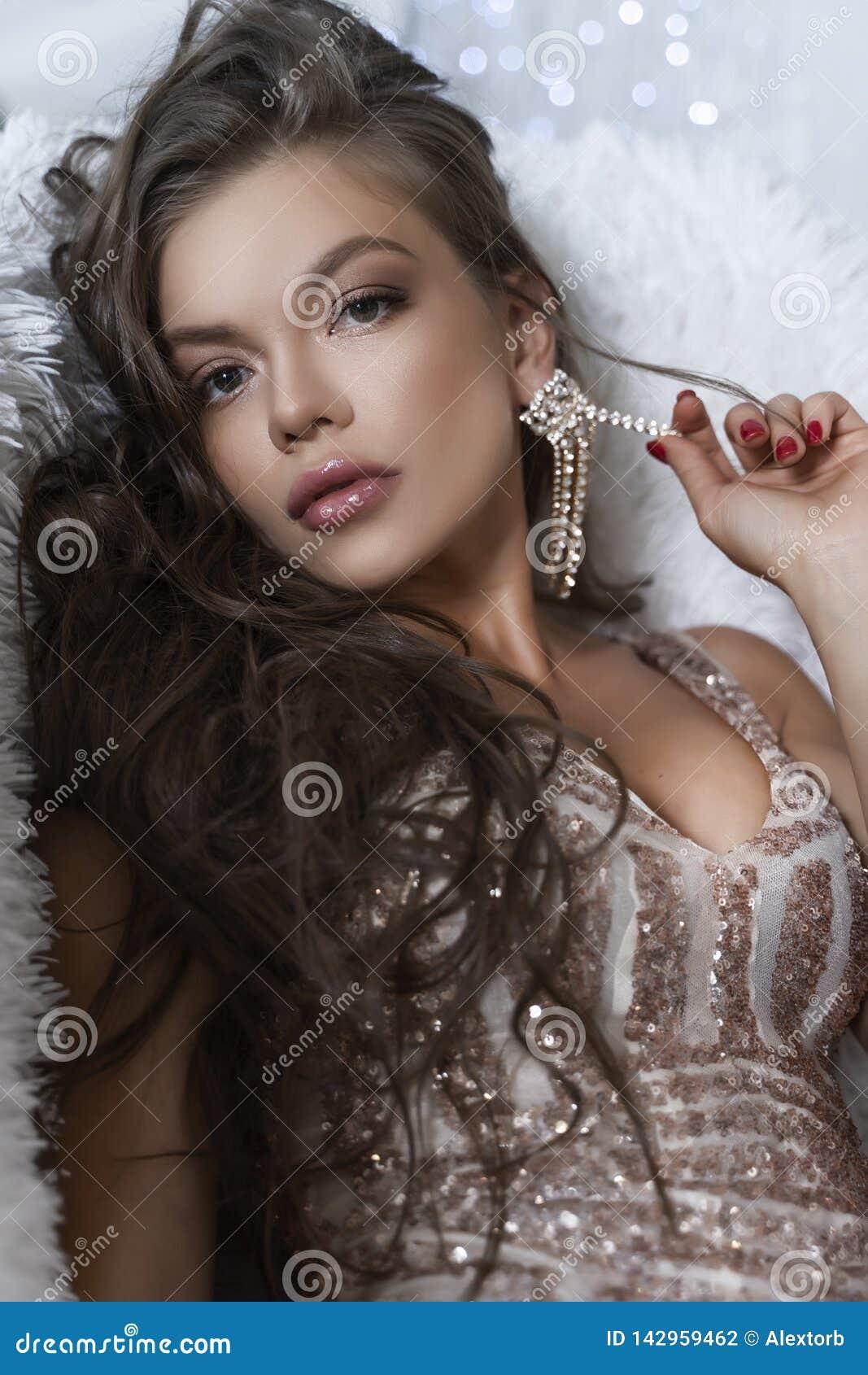 Den härliga långbenta unga sexiga eleganta flickan med stora bröst och att bära en briljant åtsittande klänning och stiletter läg