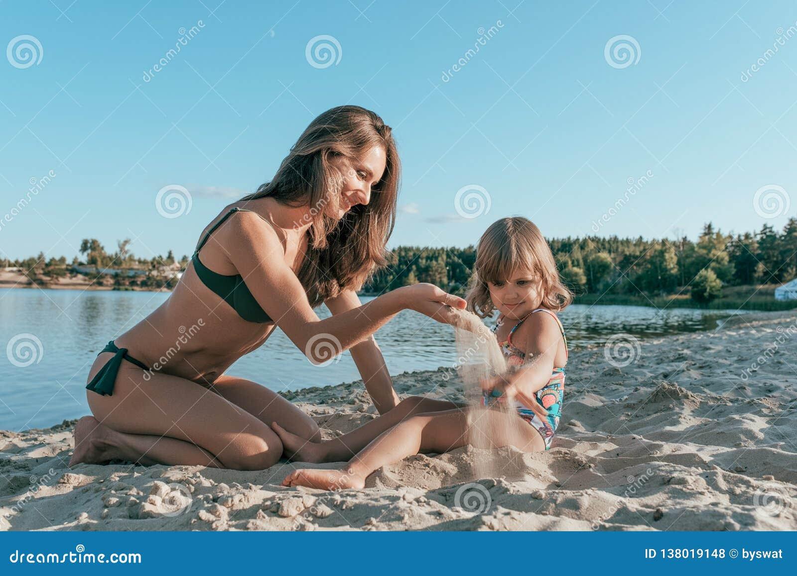 Den härliga mamman för den unga kvinnan som spelar på kust av en sjö med sand, bredvid ett småbarn, är en dotter, lyckligt le,