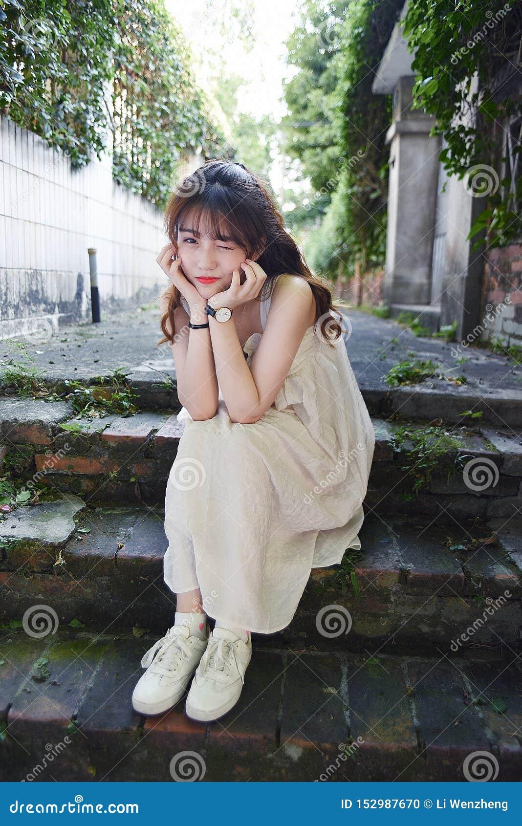 Den härliga och älskvärda asiatiska flickan visar att hennes ungdom i parkerar