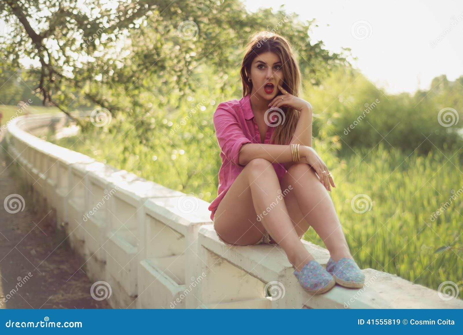 Den härliga och attraktiva kvinnan som rymmer hennes hand i hennes kind och att sitta på en konkret sida, bärande sexig tillfälli