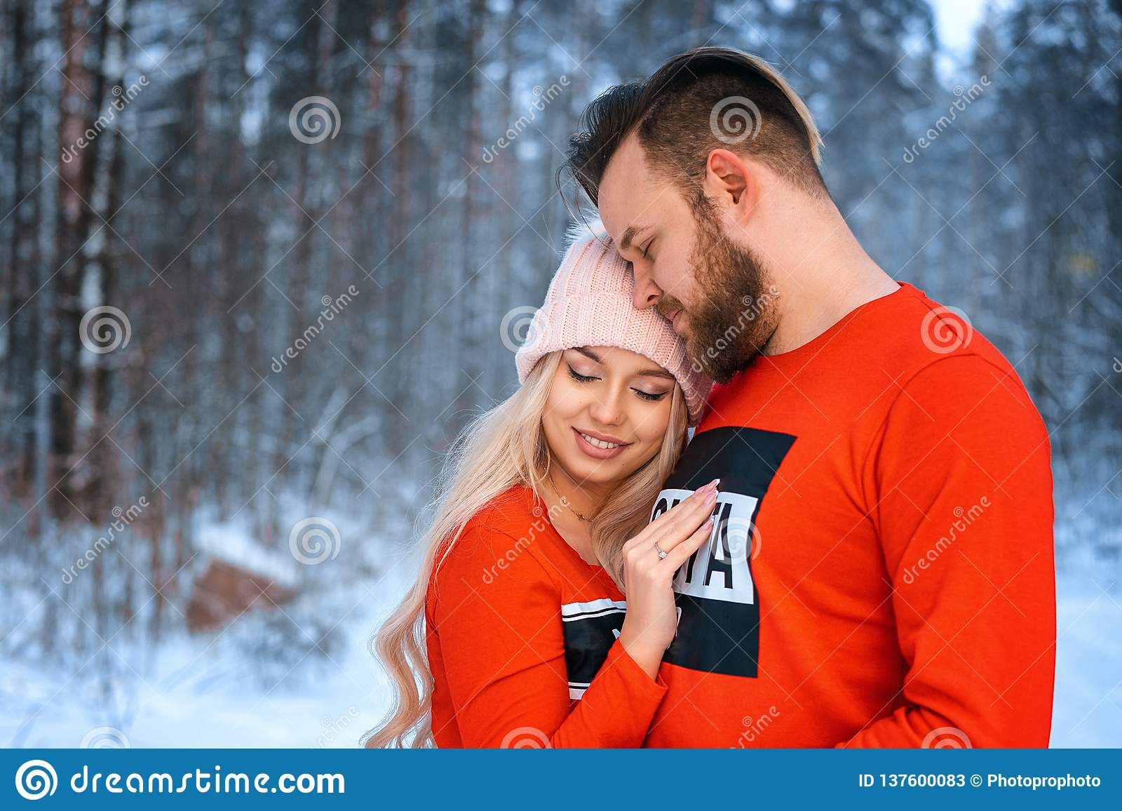 Den härliga paranseendearmen i arm i den röda tröjan i bakgrunden av skogen i vinter, går i vinterträna