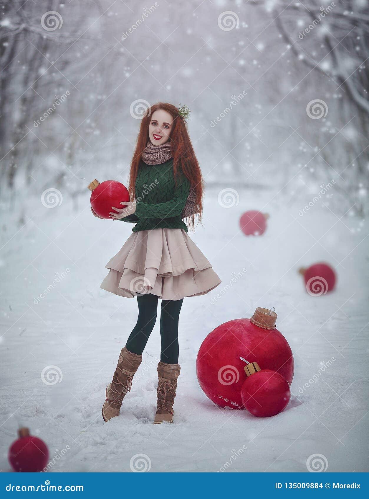 Den härliga rödhåriga flickan som en docka med röda bollar för enorm jul går i julkortet för den felika skogen för vintern