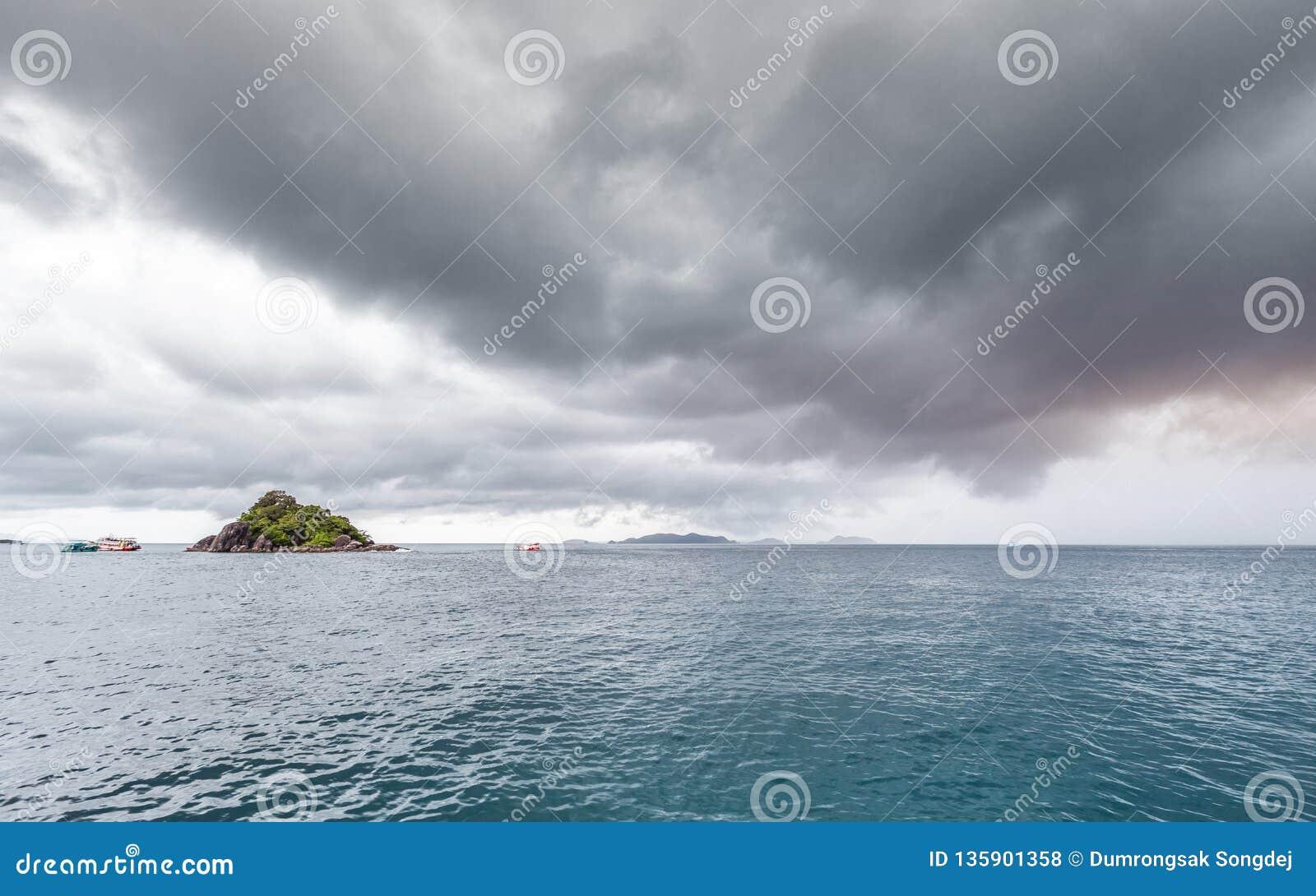 Den härliga sceniska ön med att resa fartyget, medan regna strom nära, kommer