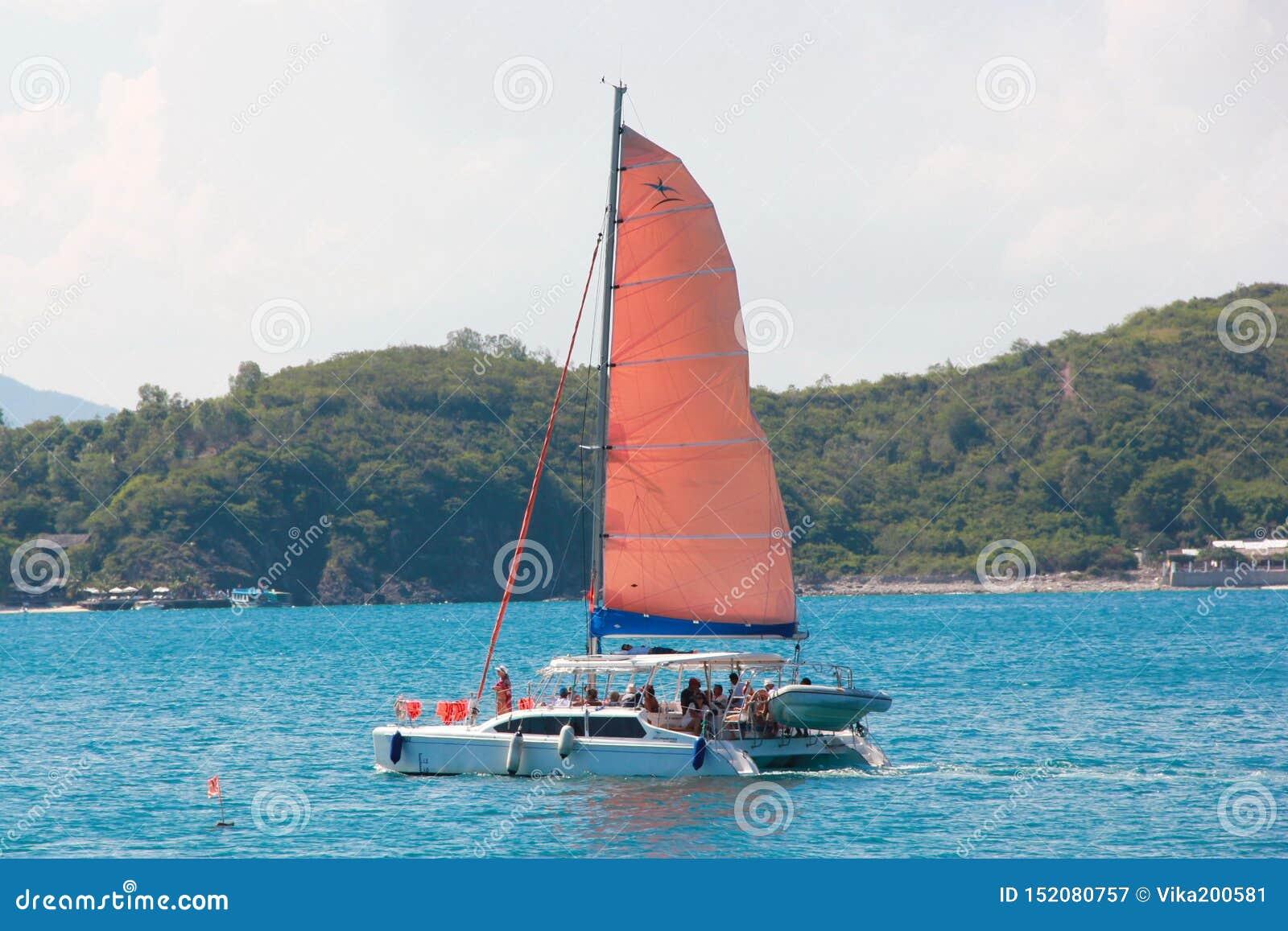 Den härliga segelbåten med ett rött seglar i havet nära stranden Bl?tt hav i soligt v?der
