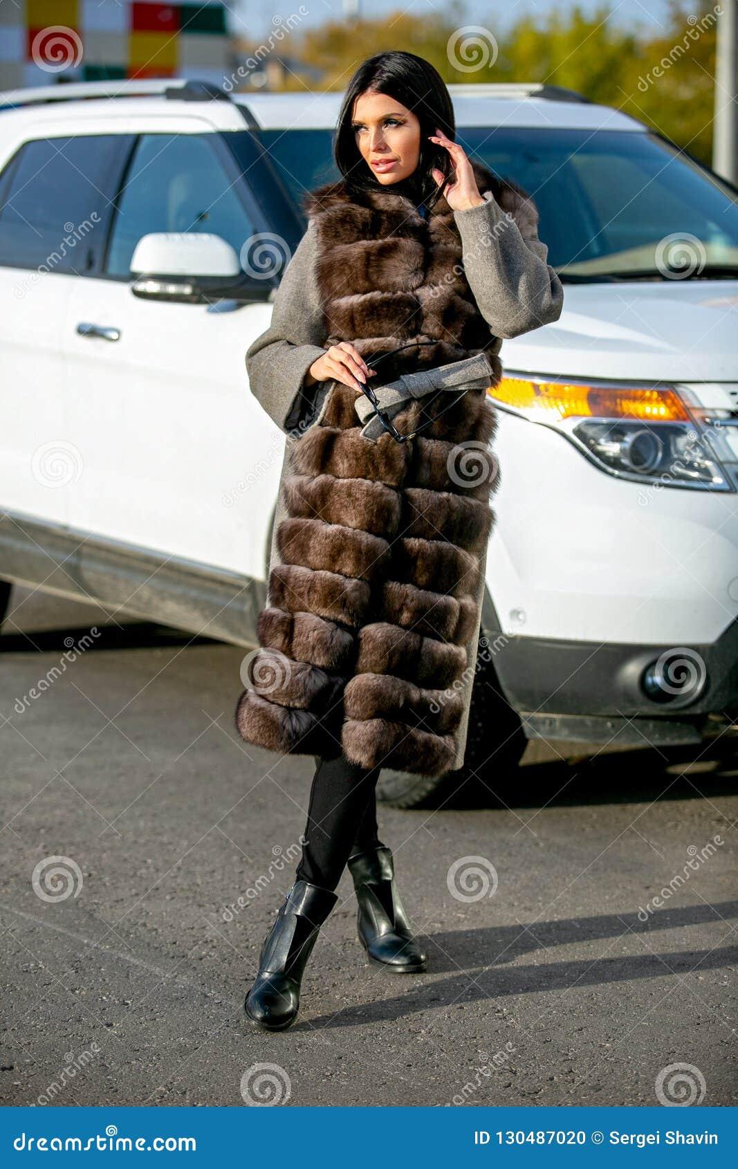 Den härliga sexiga brunetten i solglasögon och ett pälslag går ner gatan på solig dag och ser bort Sen höst eller tidig winte