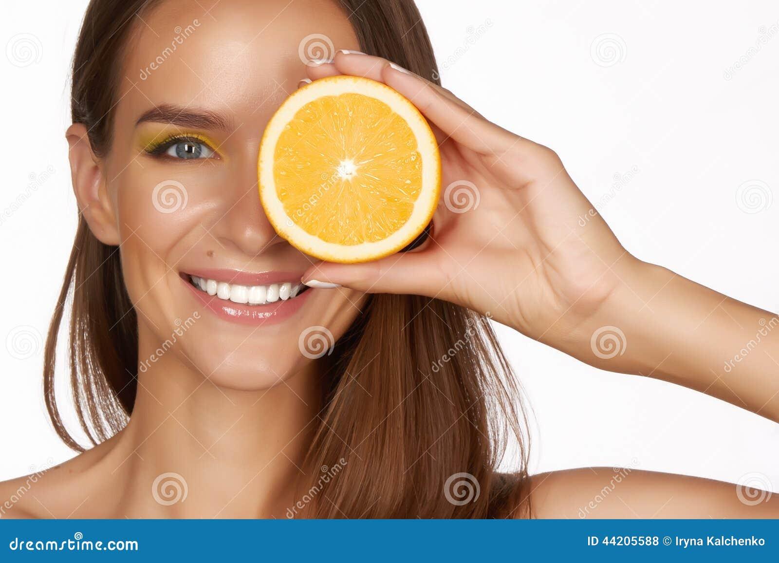 Den härliga sexiga brunettkvinnan med citruns på en vit bakgrund, sund mat, smaklig mat som är organisk bantar, ler sunt