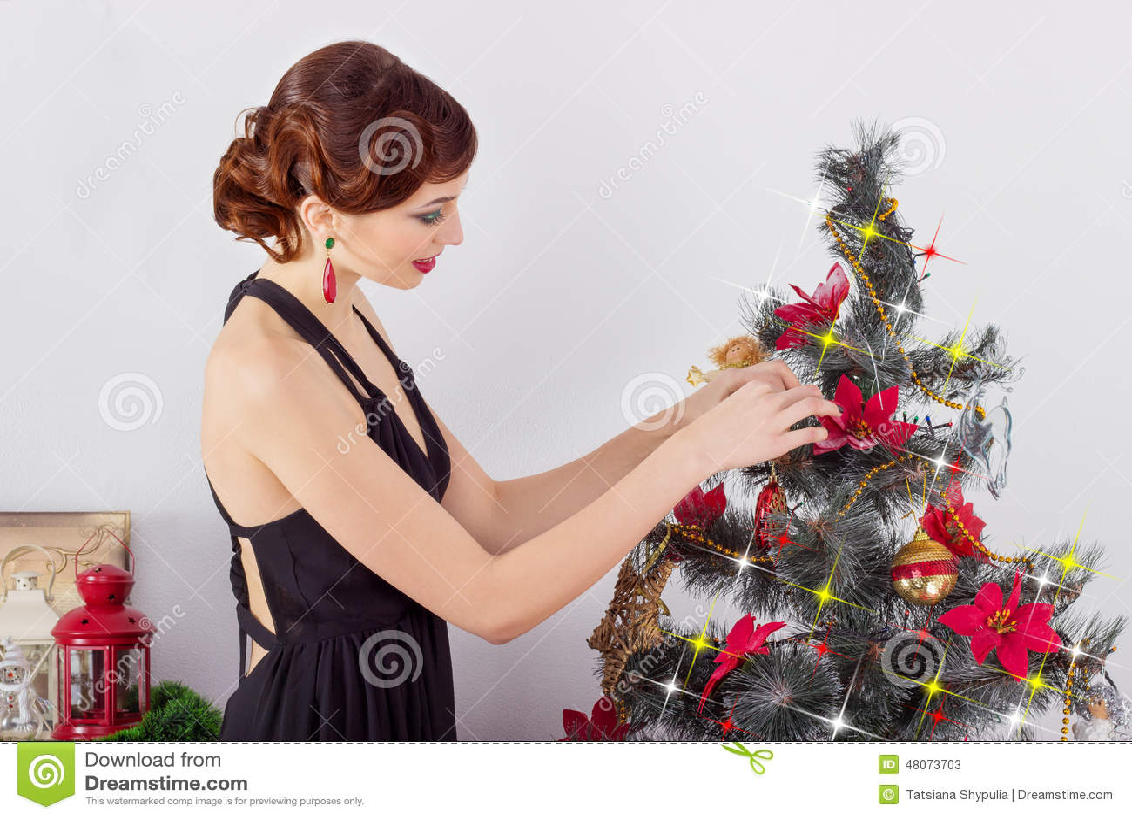 Den härliga sexiga lyckliga le unga kvinnan i aftonklänning med ljus makeup med röd läppstift, dekorerar en julgran