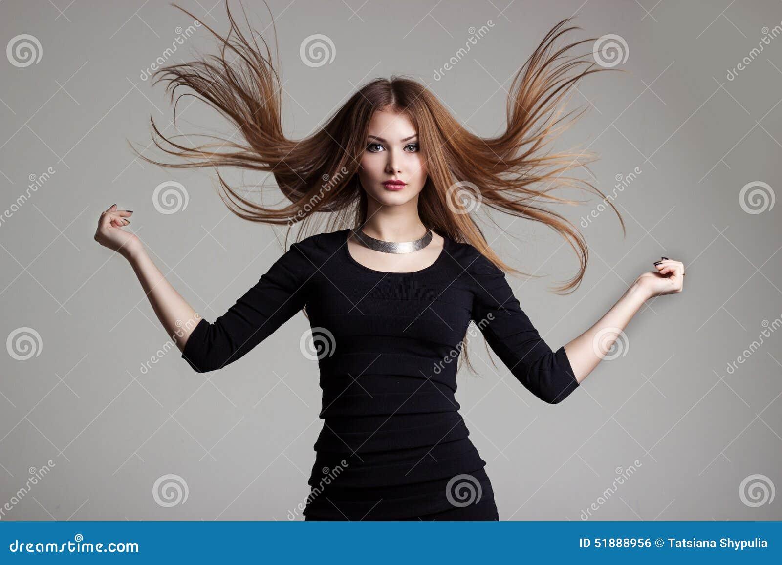 Den härliga sexiga unga kvinnan i en svart klänning med ljus makeup kastar rött hår