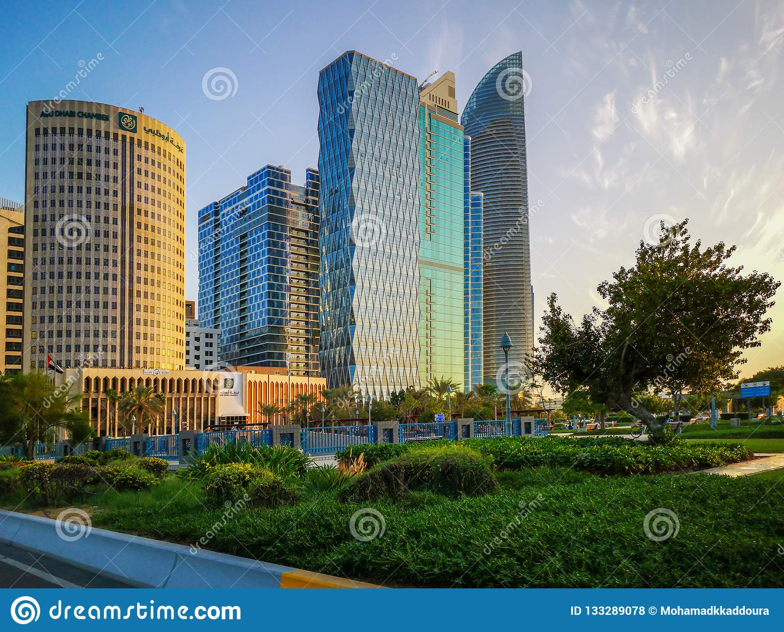 Den härliga sikten av den Abu Dhabi staden står högt, byggnader och parkerar på solnedgången från cornichen