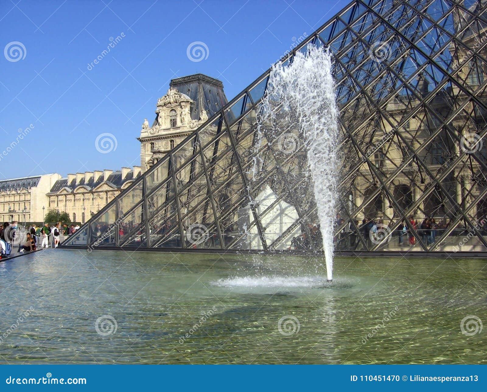 Den härliga sikten av Louvremuseet glasade pyramiden och springbrunnen med vattenstrålen