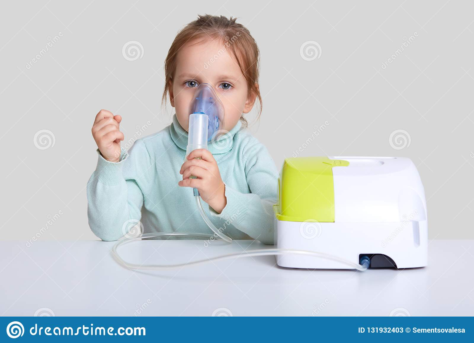 Den härliga sjuka flickan har inandningterapi, bärbar nebulizer för bruk, rymmer maskeringsdunsten, sitter på det vita skrivborde