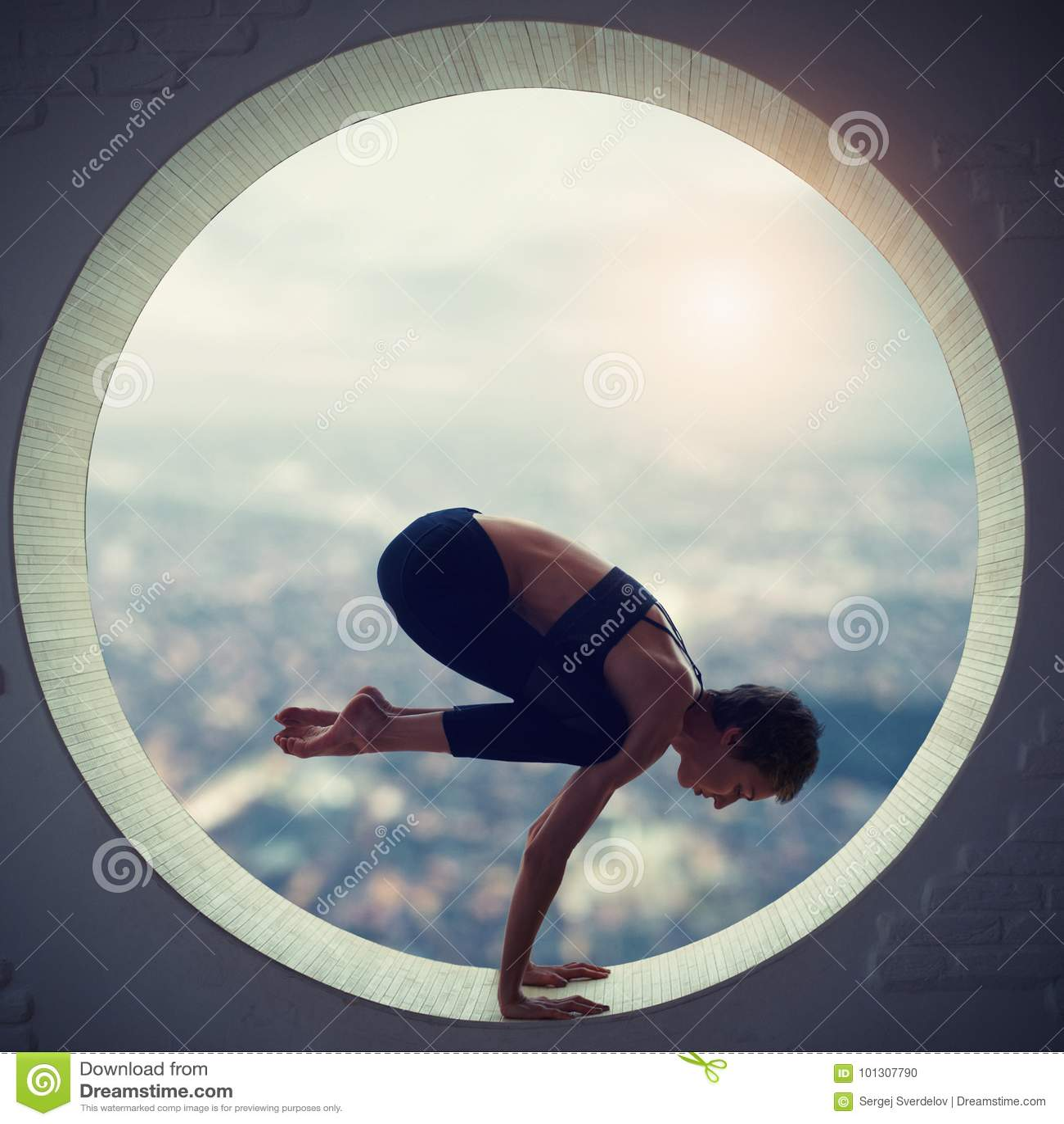 Den härliga sportiga passformyogikvinnan öva yogaasanaen Natarajasana - Lord Of The Dance poserar i ett runt fönster