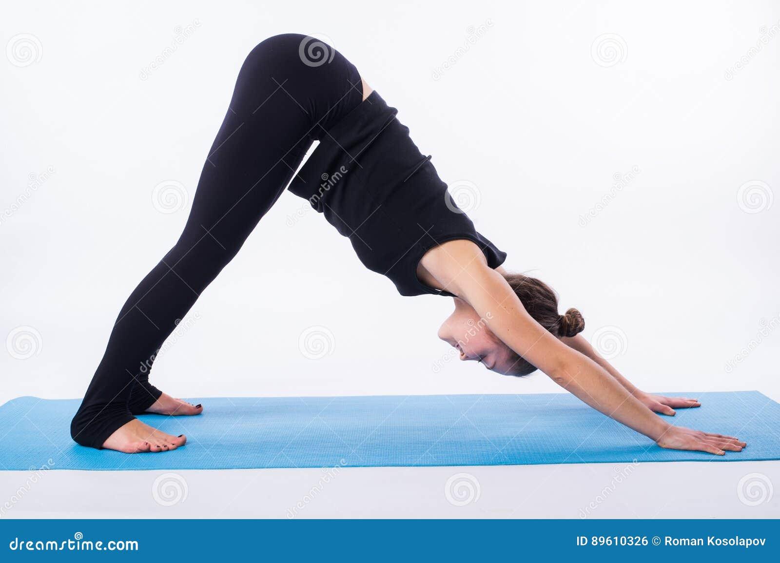 Den härliga sportiga passformyoginikvinnan öva svanasanaen för yogaasanaadhomukhaen - nedåt - som vänder mot hunden, poserar isol