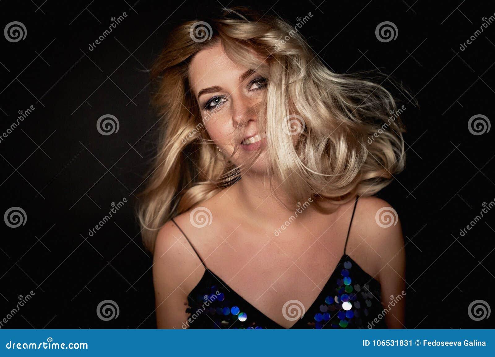 Den härliga unga blonda kvinnan med yrkesmässig makeup Smokey synar Hår som fladdrar i dans