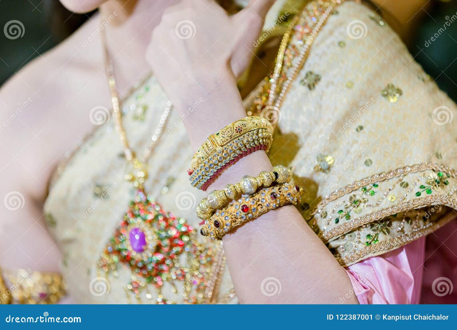 Den härliga unga bruden lägger händer på guld- armband för varvkläder på hennes handled och bröllopdiamantcirkel,