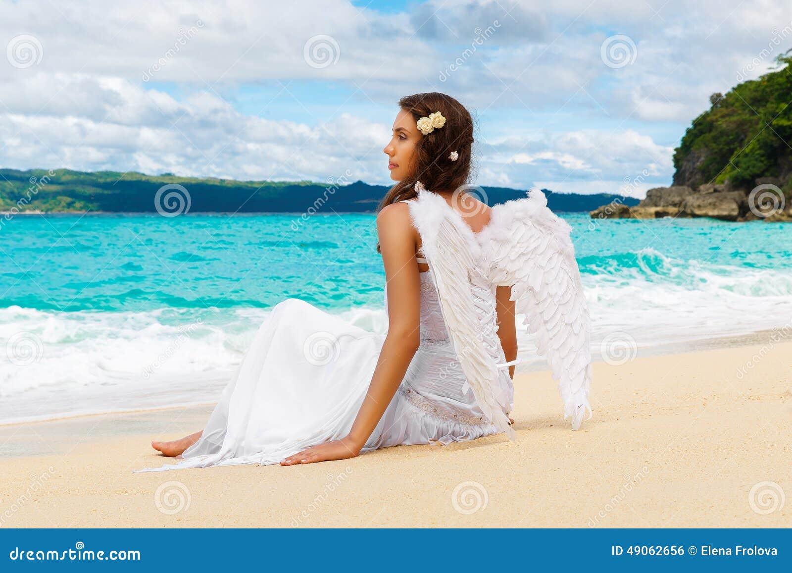 Den härliga unga bruden med ängel påskyndar på havskusten Tropica