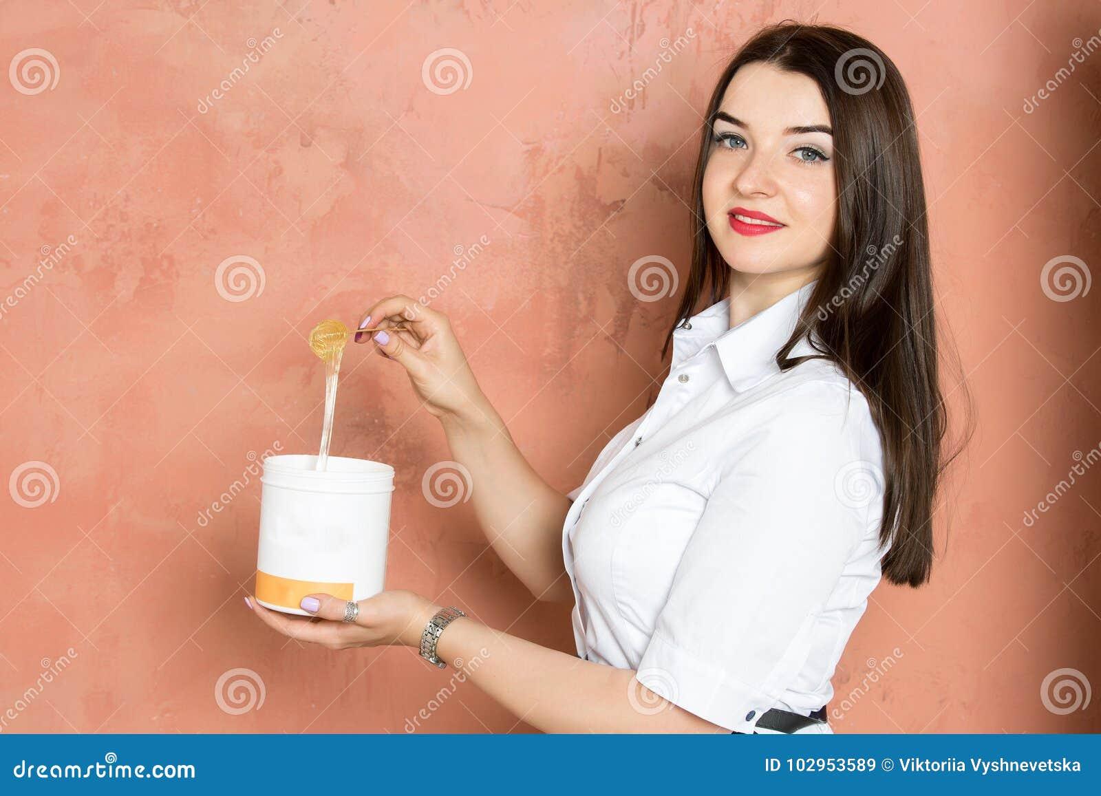 Den härliga unga brunettflickan i den vita klänningen rymmer en krus med lim, vaxet, socker Skönhetbransch