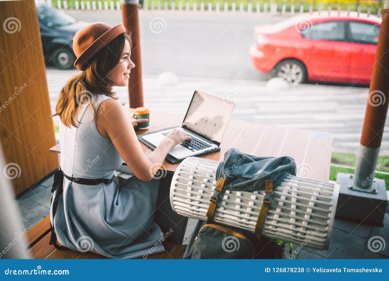 Den härliga unga caucasian valpen som sitter på en terrass i ett kafé i sommar på en trätabell i en hatt och en platta, använder