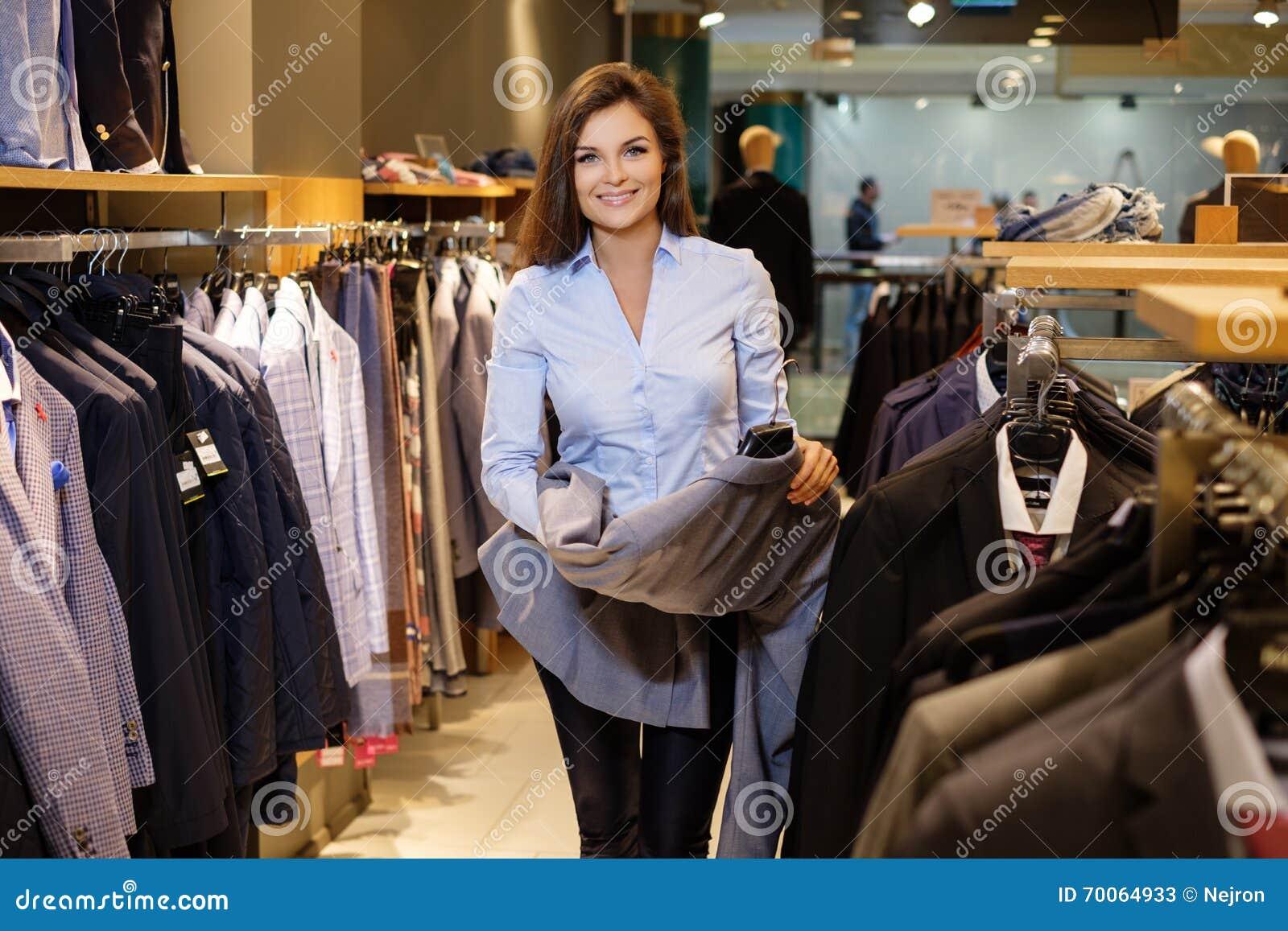 Den härliga unga försäljaren hjälper kunden att välja ett omslag i dräkt shoppar