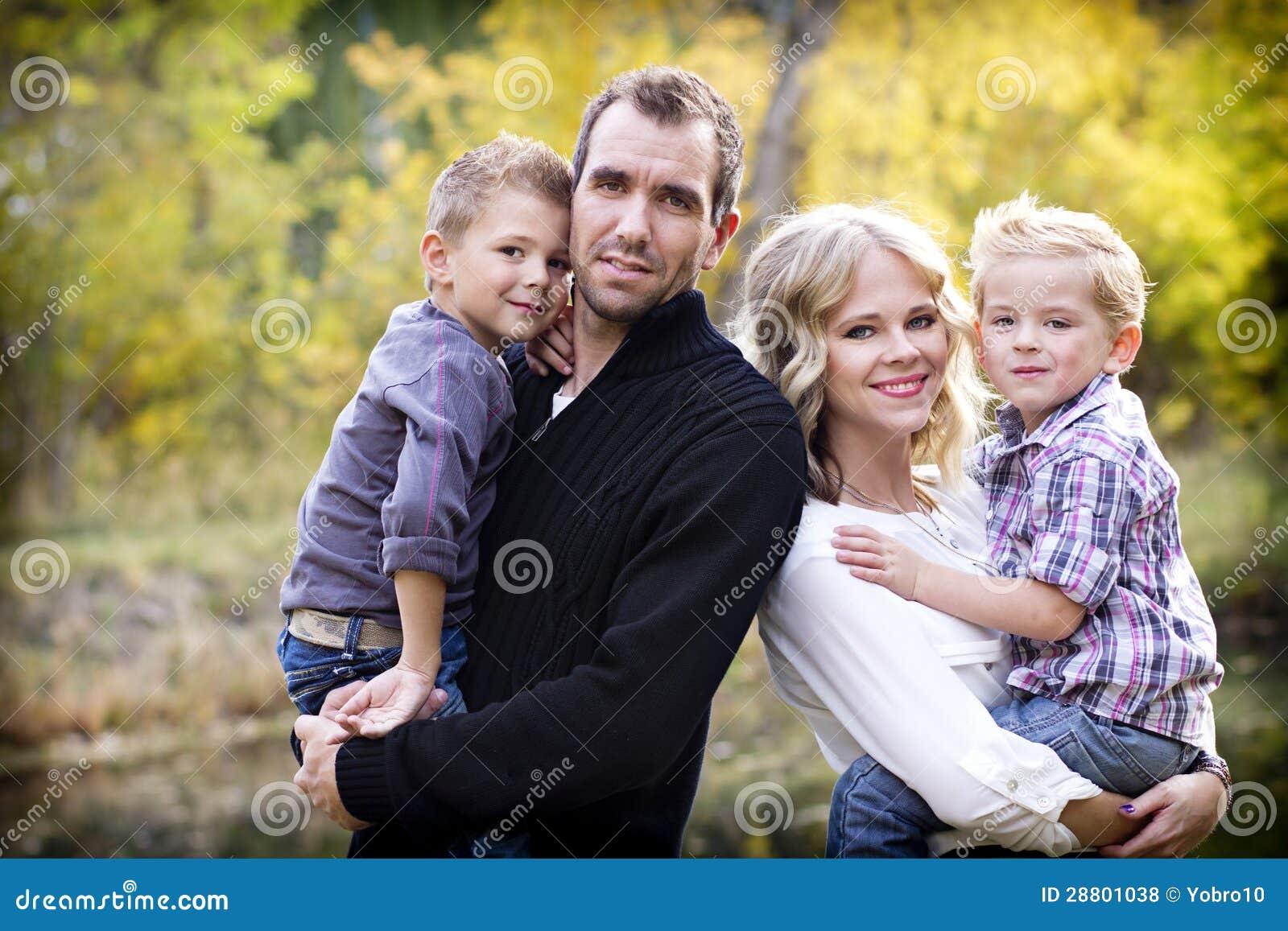 Den härliga unga familjståenden med nedgången färgar