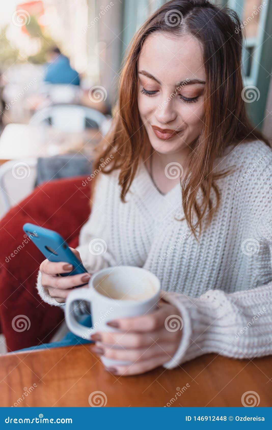 Den härliga unga flickan i utomhus- bruk ilar telefonen och att smsa
