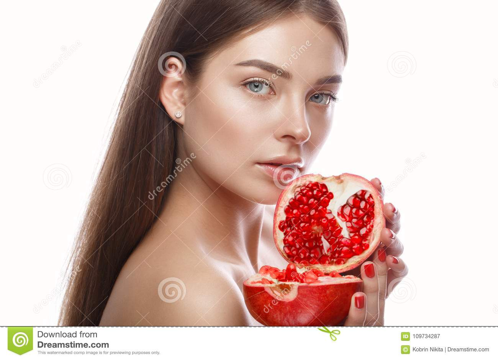 Den härliga unga flickan med ett ljust naturligt smink och gör perfekt hud med granatäpplet i hennes hand Härlig le flicka