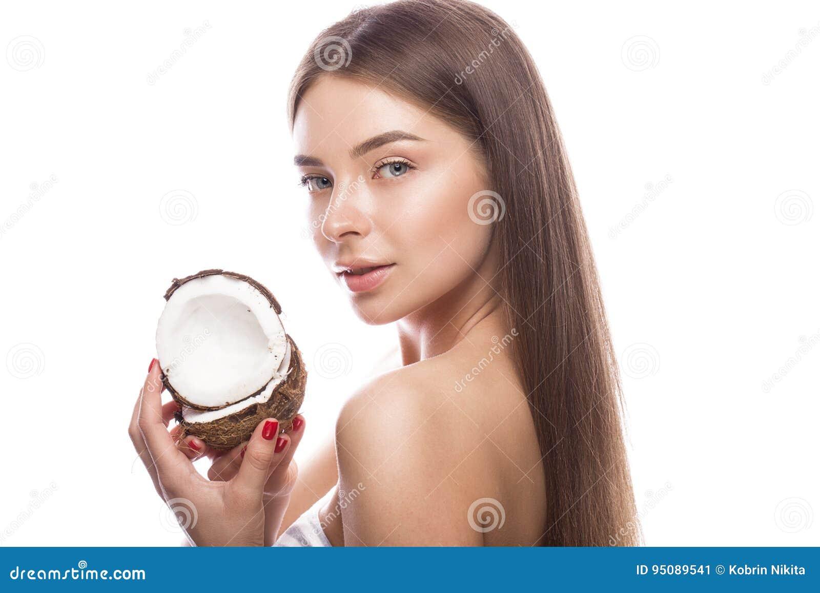 Den härliga unga flickan med ett ljust naturligt smink och gör perfekt hud med kokosnöten i hennes hand Härlig le flicka