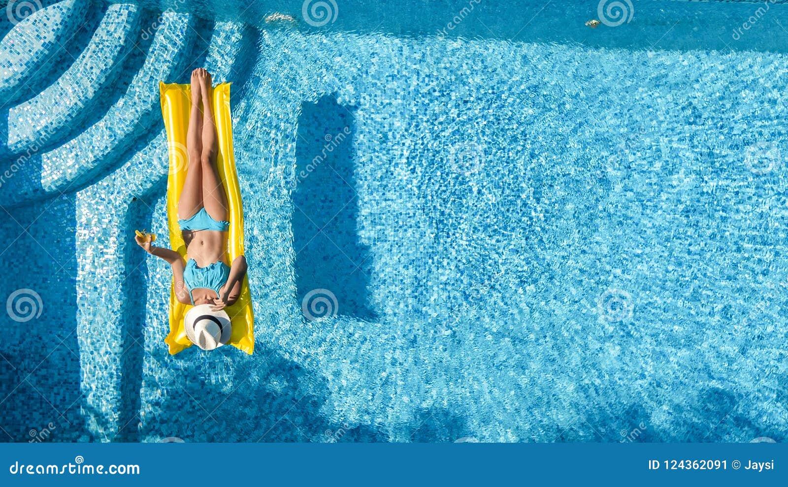 Den härliga unga flickan som kopplar av i simbassängen, bad på den uppblåsbara madrassen och, har gyckel i vatten på familjsemest