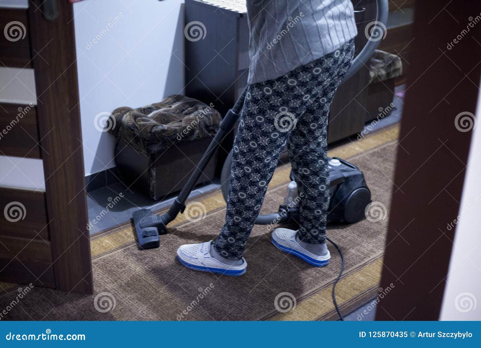 Den härliga unga kvinnan använder en dammsugare, medan göra ren golvet hemma