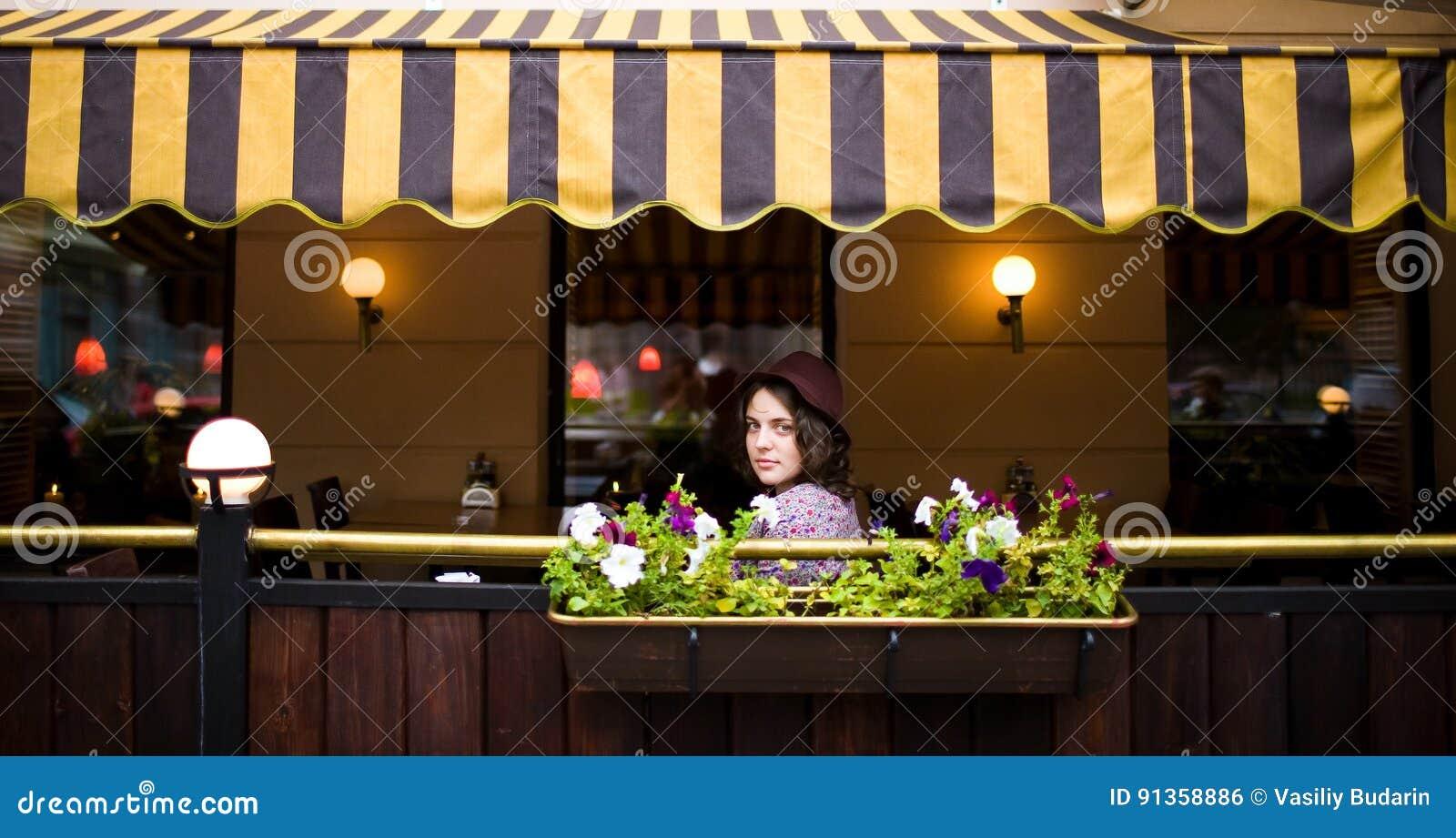 Den härliga unga kvinnan i en hatt sitter på en terrass i ett kafé och ser kameran