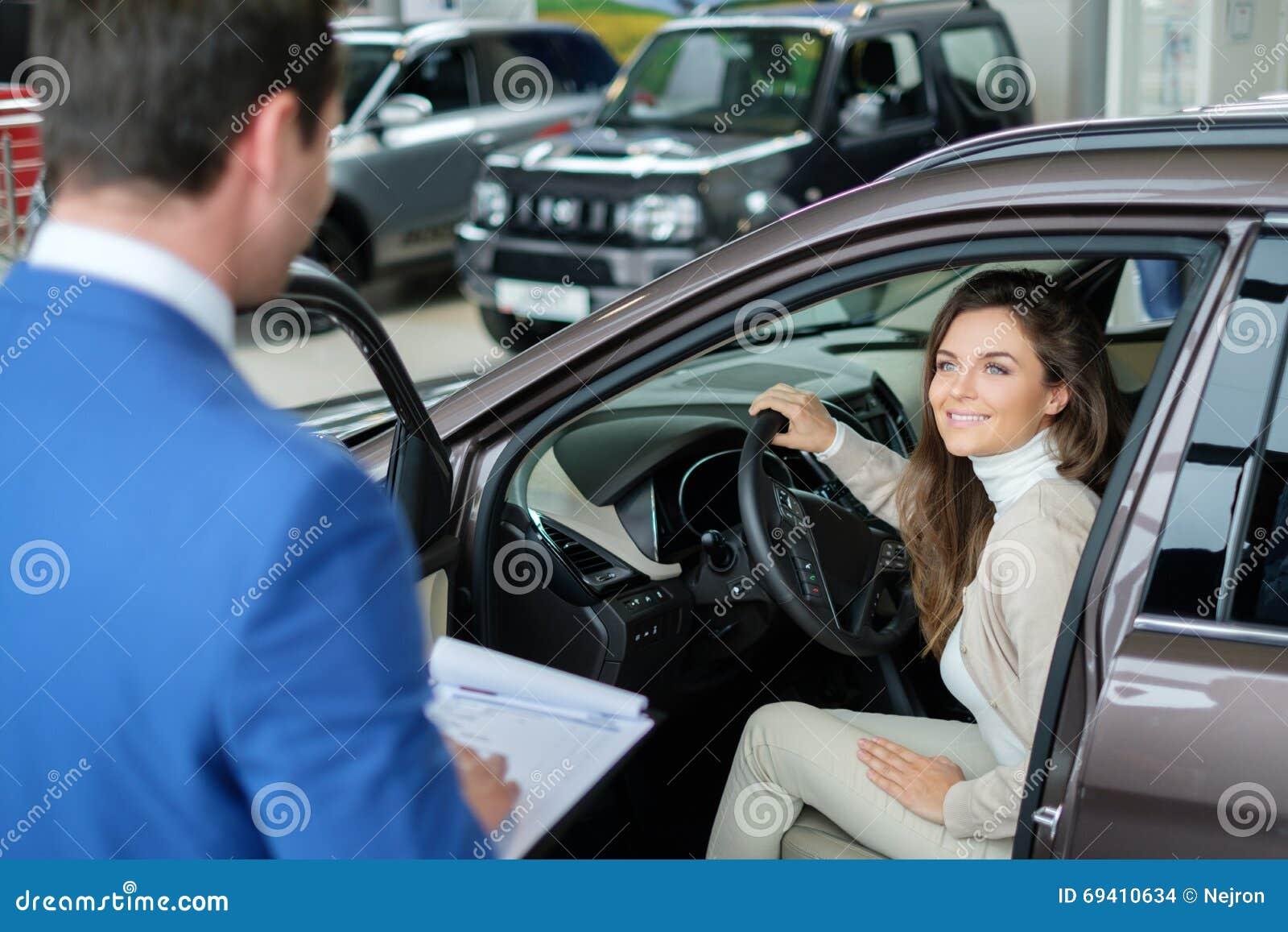 Den härliga unga kvinnan köper en bil i återförsäljaresalongen